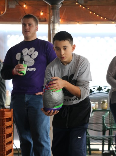 Photos/Kyla Hurt P.A.W.S. volunteer Seth Evans puts on his serious face to bowl for a great cause. Oddly, the frozen turkeys can pick up a good amount of speed.