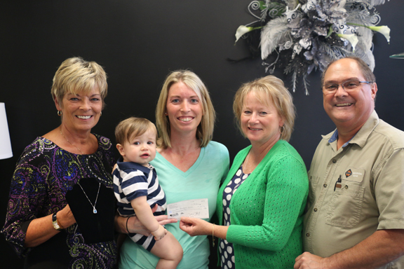 "Joyce Hembrough of Duncan & Hoots Jewelry stands with the donated necklace (on left). Pictured with Hembrough are Lindsay Stiltz, Crue Stiltz, Crystal and Randy Chappell. Randy and Crystal Chappell, maternal grandparents of Asher, were present to accept the check on behalf of the family, as Brett and Alicia have been staying primarily at Barnes with Asher. The gratitude was apparent through the tears and hugs of the Chappells. When Alicia Brockhouse found out about the donation, she was ""crying with appreciation."""