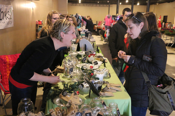 """1. Khara Koffel, one of the """"two chicks"""" behind locally made Serious Lip Balm enjoys a conversation concerning commitment to flavor choices with shoppers at Small Business Saturday."""