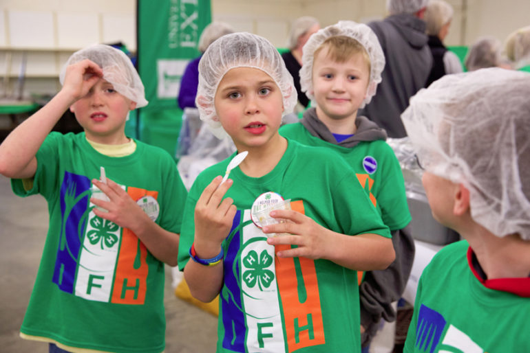 4-Hers eat samples of a casserole at the start of the workday.