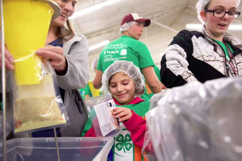 Seven-year-old Addy Dennis of Arenzville fills a bag. She was volunteering with the Neighborhood Guys and Gals 4-H Club of Winchester.The one millionth meal for families in need was packaged by 4-H volunteers Wednesday evening at the Morgan County Fairgrounds in Jacksonville. The state-wide program started in 2013, with 4-H members and others packaging the meals. Volunteers from Cass, Morgan, Scott, Greene and Calhoun were on hand to put together meals Wednesday. The 31st box of the night pushed the program past the one million mark.Wednesday 4 April 2018Photos by Steve of Warmowski Photography for The Source http://www.warmowskiphoto.com 217.473.5581 - 180404