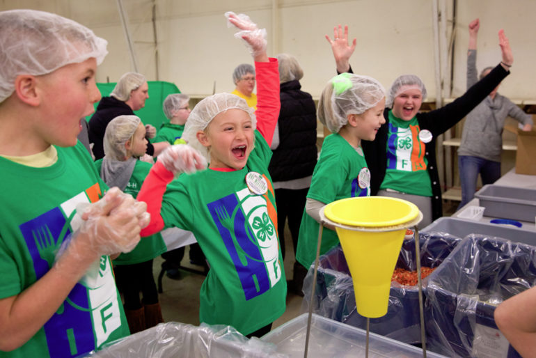 Members of the Berea Ag 4-H Club of Alexander cheer as they complete a box with the 36th meal.The one millionth meal for families in need was packaged by 4-H volunteers Wednesday evening at the Morgan County Fairgrounds in Jacksonville. The state-wide program started in 2013, with 4-H members and others packaging the meals. Volunteers from Cass, Morgan, Scott, Greene and Calhoun were on hand to put together meals Wednesday. The 31st box of the night pushed the program past the one million mark.Wednesday 4 April 2018Photos by Steve of Warmowski Photography for The Source http://www.warmowskiphoto.com 217.473.5581 - 180404