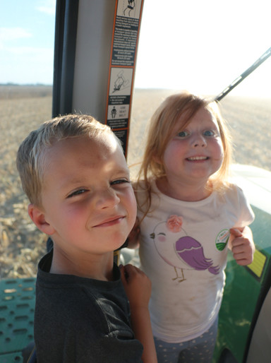 "Meet my co-riders inside the tractor,  Brayden Richardson and Leta Sheeley. The two 5-year-olds were talkative on the adventure. When watching the corn fly through the air into the trailer, Sheeley exclaimed, ""It looks like it's exploding!"" ""Yea, like a volcano,"" added Richardson."
