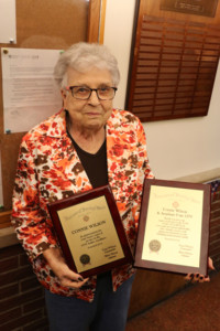 Connie Wilson stands proudly with the plaque awarded to her for years of service.