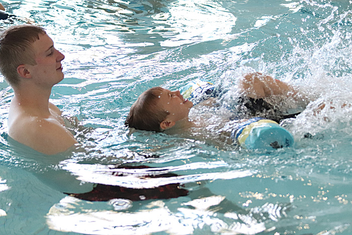 Photo/Lynn Colburn Adult swimmers help young kids gain confidence in the water during a swim class held at the Bob Freesen YMCA.