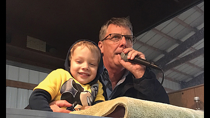 Photo/Special to The Source Newspaper  Grandson Otto wanted to join Jess Spradlin up on the mic at an auction.