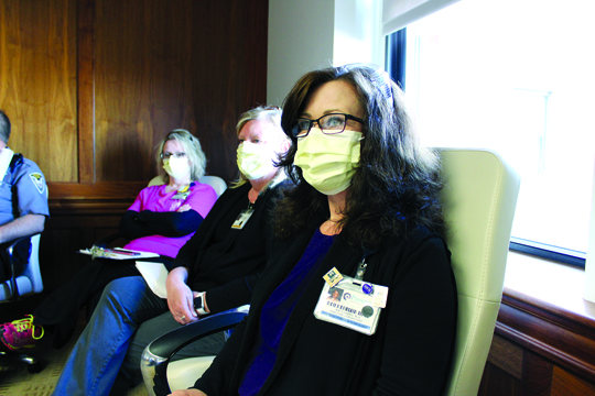 Misty Farris, Passavant Area Hospital laboratory director, listens during a meeting of hospital leaders. At the hospital, all members of a group engaged in a meeting for more than 10 minutes must wear a face mask. This is for the protection of each person in the meeting as face masks help contain respiratory droplets produced when people speak, cough or sneeze.