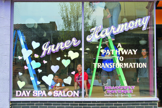 Photo/Marcy Patterson  Cheryl Kearns, the owner of Inner Harmony Salon and Spa, makes good use of her forced closure to clean and paint her salon. Her daughter, grand kids and grand dog, helped with the efforts inside the window on South Main Street in Jacksonville last week.