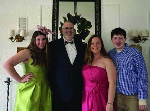 """McGuire – The Art Association of Jacksonville cancelled the 63rd annual Beaux Arts Ball scheduled for Saturday, April 25, 2020. Megan McGuire and Sara Schumacher were co-chairs for this year's event. McGuire and her family celebrated the """"Run for the Roses"""" theme at home. McGuire stated it was a night filled with laughs. Her family dressed up, posed for a photo, and immediately got back into sweatpants and enjoyed pizza. She stated she and her husband Ryan did enjoy a Mint Julep in honor of the Kentucky Derby Theme. Ryan, Megan Alex, and Claire"""
