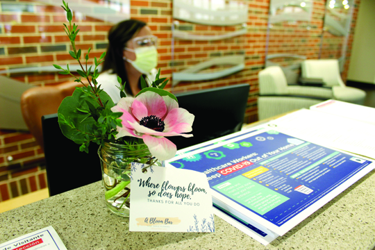 Flower donation: A fresh flower in a vase, one of eight bouquets donated by A Bloom Bar to honor healthcare workers, looks pretty on the information desk in the main lobby of Passavant Area Hospital. Due to visitor restrictions at this time, all tokens of encouragement as well as donations of food and supplies to the hospital must be prearranged by contacting Pam Martin at Martin.Pam@mhsil.com