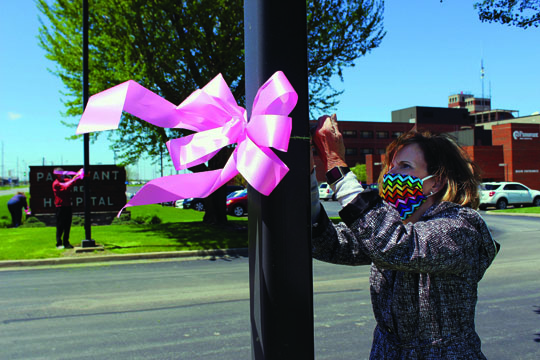 Photo/Bre Linstromberg-Copper Ginny Fanning, Passavant Area Hospital Foundation trustee and member of the hospital's board of directors, defies the windy weather to tie a pink ribbon to a light post at the main entrance to the hospital's campus. Fanning was joined in the effort by Mary Fergurson, Foundation board president; Steve Turner, Foundation board treasurer; and Pam Martin, Foundation executive director. The pink ribbons are part of a campaign to show support and appreciation for healthcare workers.