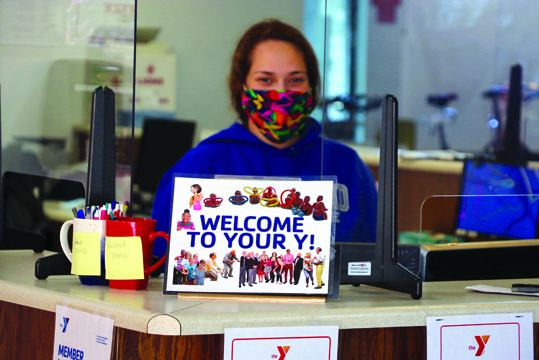 Olivia Bobb, staff member at the Bob Freesen YMCA (Y), stands behind the reception area. The Y reopened Monday, June 1 with restricted hours of Monday through Friday from 6 a.m. - 7 p.m. and Saturday from 7 a.m. - 4 p.m. Note, however, that 1 - 2 p.m. is closed daily for cleaning.