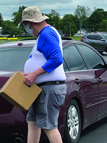 Kiwanis member Charlie Rice delivers a box full of fresh groceries into a waiting car.