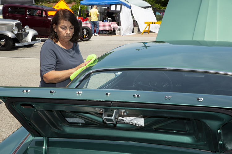 Barb Wise, of Springfield, polishes up her 1969 Mustang E. She and her husband, Tim, refurbished the car after buying it six years ago, including switching fromyellow to the original green. Only 96 of the E cars were made, to compete in the Mobilgas Economy Run that would take cars from coast to coast, to see which could deliver the bestgas mileage.