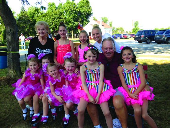 Eleanor and Dr. Tom Stevens pose for a photo with dancers in recital outfits.