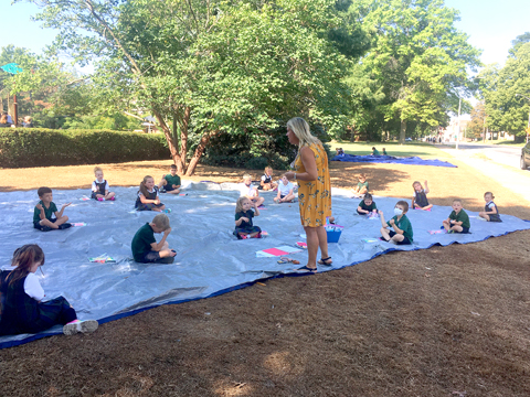 Photo Submitted to The Source Our Saviour kindergartners work on the letter T while sitting outside with Mrs. Chumley.