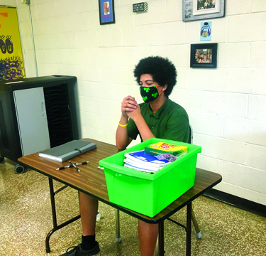 Photo Submitted to The Source Teachers in the junior high rotate amongst all classrooms to optimize safety precautions and maximize student learning. Trey G. sits at a table in his eighth grade classroom at Our Saviour School.