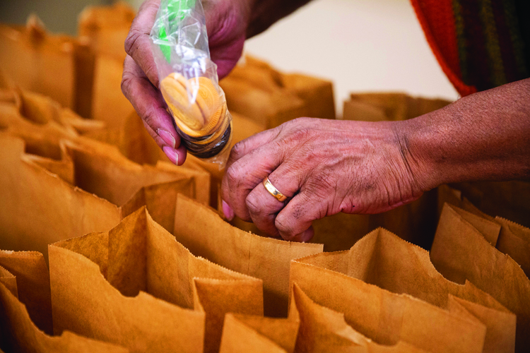 """Charles Lockhart adds cookies to dessert bags. Lockhart volunteers every day at the soup kitchen. The Alton native moved to Jacksonville after a stint of living on Chicago's south side, and said he started volunteering the second day of living in town. """"A lot of our volunteers come once, then they become long-time volunteers,"""" said Pulley. -  Polly Pulley and her volunteers at the Spirit of Faith Soup Kitchen in Jacksonville, photos for The Source, Thursday 4 February 2021Photos by Steve & Tiffany of Warmowski Photography http://www.warmowskiphoto.com 217.473.5581 - 210204"""