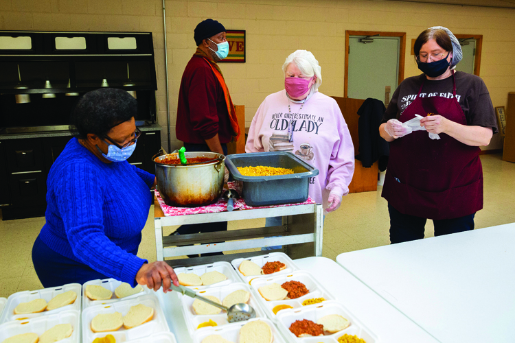 Polly Pulley, Charles Lockhart, Nancy Scott and Kim Edmonds (from left) put the final touches on meal packages. Pulley noted that Scott not only prepares meals every Thursday, but she also volunteers as a grant writer.- Polly Pulley and her volunteers at the Spirit of Faith Soup Kitchen in Jacksonville, photos for The Source, Thursday 4 February 2021Photos by Steve & Tiffany of Warmowski Photography http://www.warmowskiphoto.com 217.473.5581 - 210204