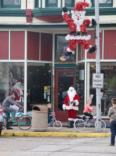 "Photo/Kyla Hurt. Good ole' St. Nick walked the town during the event, as well. Three young cyclers had just stopped to say ""hi,"" in return for some stocking stuffers and a jolly ""ho-ho-ho!"""