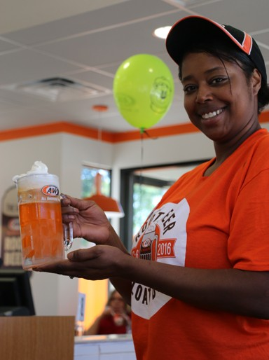 "Then, there's the menu, featuring ""All American Food."" Perry presents one of her favorite sweet items, which ""is like an orange creamsicle."" It's an ice cream float using Tropicana Orange Twister soda"