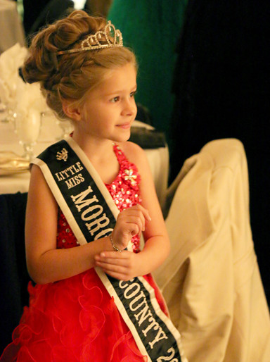 2016 Little Miss Morgan County Fair Olivia Haverfield, daughter of Michelle Kays and Brad Haverfield of South Jacksonville, watches as her fellow royalty are photographed with the event's lit backdrop.