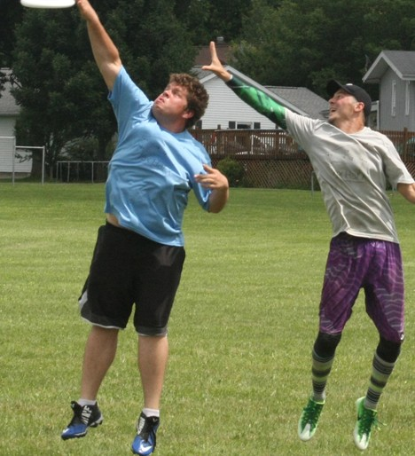 Andrew Mueller, left, of Decatur, jumps to block a pass as Gabriel Posluszny, of Urbana, reaches for the disc.