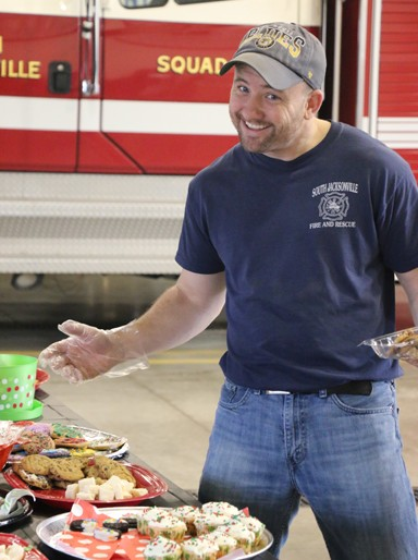 Photo/Kyla Hurt, Many of the Auxiliary members noted that this was one of the best years ever.  With only a table of cookies left by mid-morning, Ryan Deeder lends a hand and some Christmas cheer on behalf of a call-in order.