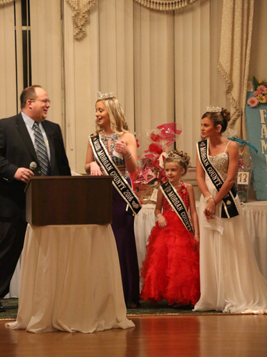 Jay Harris turns over the microphone to members of the 2016 Morgan County Fair royalty. They include (from left): Queen Taylor Zoerner, Junior Miss Kaylee Ford and Princess Olivia Haverfield.