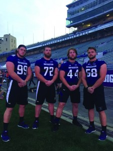 Former Jacksonville Crimson Blake Hance (No. 72) stands on Northwestern's Ryan Field with his Wildcat teammates Ben Oxley (No. 99), James Prather (No. 44) and Heath Reineke (No. 58).
