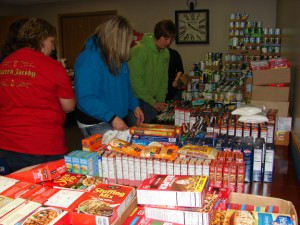 CCMHA staff sort and prepare over 4,000 food items for food baskets for the families they serve. Pictured are Associate Director Stacey Rock, Jennifer Cooper and Executive Director Diana Feigl.