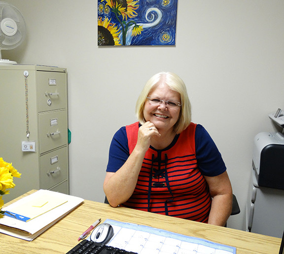 Showing the beautiful smile that lights up her face, Hungerford in her office at the Morgan County Health Department on June 20, 2017 just prior to her retirement. The painting she used as a sample during her church paint-and-pour sits on the wall behind her desk. Another beautiful sample of her art is on the wall next to her desk and not seen in the photos.