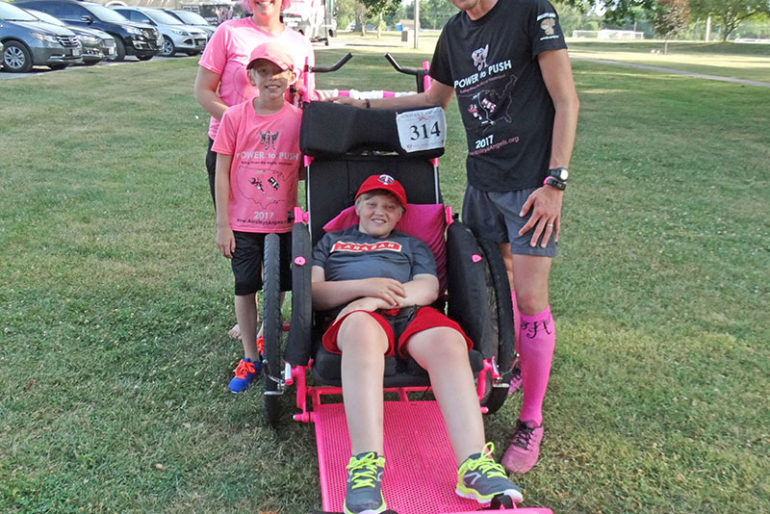 The Evans family from New York is running the length of the 'Mighty Mississippi' this summer in 29 days. Pictured left to right: mother, Nichole, and younger brother, Simon, who both provide support along the route; Shamus (in the large jogger chair) and Shaun, who run the entire way. The Evans family knows how receiving assistance from Ainsley