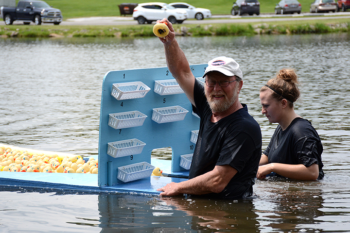 Bruce Selway holds the winning duck for everyone to see. His daughter, Katie, assisted him at the finish line.