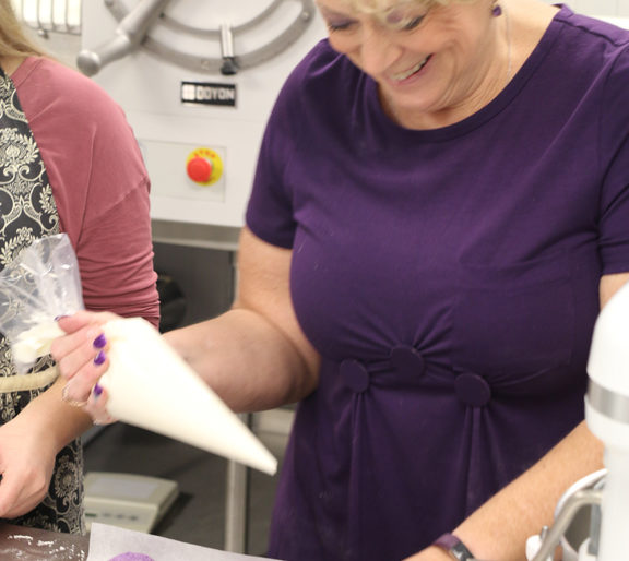 Instructor Terri Branham laughs with the class as she demonstrates how to pipe the macarons correctly.