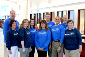 Members of the Jacksonville Savings Bank wearing their 100-year celebration shirts include (from left to right): Shawn McCombs, Susan Wood, Stephanie Rich, Lisa Stambaugh, Margie Martin, Shaan Smith, Tom Luber, Chris Royal and Mary Fergurson. All are members of the lending team aside from Fergurson, who is head of the trust department.