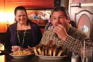 """Photo/Kyla Hurt  Brian Fitzjarrald's sister (pictured in rear) drove from Peoria to surprise him for his birthday celebration and witness his culinary clash with KJB's """"Challenge Burger."""""""