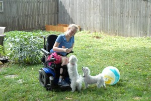LIzzie Chamberlain interacts with her dogs from her wheelchair
