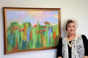 Artist Toni Long of Jacksonville stands with a smile next to one of the pair of paintings of poppies, dedicated in memory of her dear friend, Judith Beiderbecke.