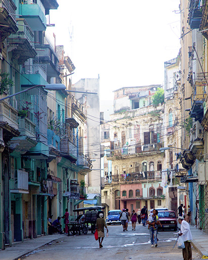 Havana in the morning - typical street scene with power lines, laundry, old cars and people living life.