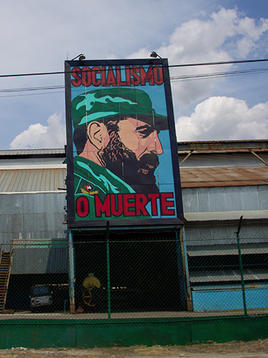 "Pro-government signs were prevented, especially along the roadways. This one says, ""Socialism or death,"" with an image of Fidel Castro."