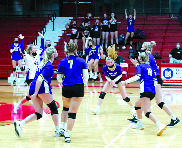 Routt Catholic High School's varsity volleyball team celebrating their victory over crosstown rival Jacksonville High school, with an ending set score of 25-22.