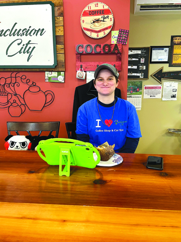 Photo/Francesca Boston Vaska Figurski, daughter of the owners of Inclusion City Shops in Pleasant Plains, smiles behind the counter of the café/car detailing business owned by her parents.
