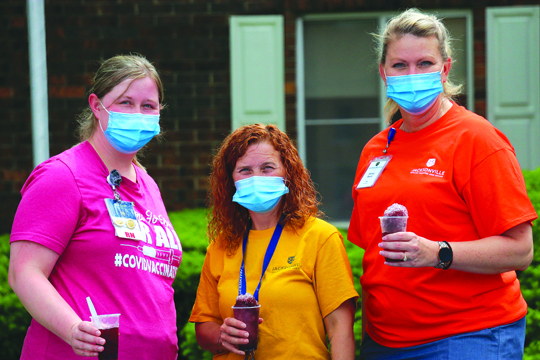 From left to right, Director of Nursing Lexi Harrell, Activity Director Hope Ingram and Registered Nurse Haley Beck, all employees of Jacksonville Skilled Nursing and Rehab, pose for a shot at the nursing facility's table that was handing out snow cones.